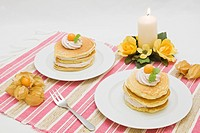 American buttermilk pancakes filled with wood berry cream, decorated with cape gooseberries and lemon balm, candle at back