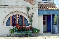 bench in front of window with roses, France, Camargue, Salin_de_Giraud