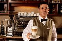Waiter serving a Latte Macchiato