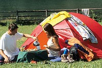 couple sitting in front of a camping tent having breakfast