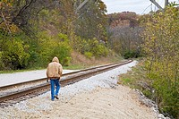 Brecksville, Ohio - A man walks along the tracks of the Cuyahoga Valley Scenic Railroad which runs along the Cuyahoga River in Cuyahoga Valley Nationa...