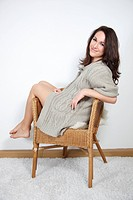 beautiful young woman sitting on rattan armchair