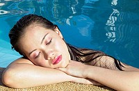 Pretty Asian young woman relaxing in swimming pool with eyes closed.
