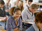 Smiling college student sitting at desk in classroom