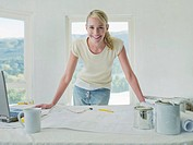 Smiling woman leaning on table with blueprints and paint