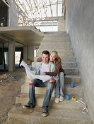 Couple looking at blueprints on staircase of house under construction