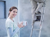 Woman holding coffee cups and man on ladder