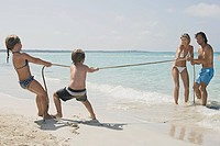 Family playing tug_of_war on beach