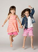 Four year old twins jumping happily in a studio setting