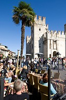 Tourists sitting in a café in front of the Scaligero Castle, Sirmione, Lake Garda, Lago di Garda, Lombardy, Italy, Europe