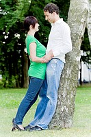 Pair in love leaning against a tree