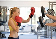 Young woman training boxing in fitness studio, side view