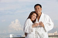 Young couple in robes hugging and smiling