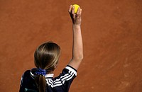 Ball girl holding up a tennis ball
