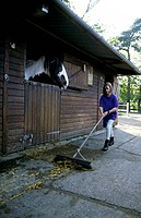 Horse rider cleans up the stables