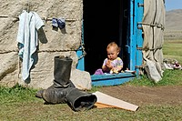 Baby, toddler sitting in the entrance of a yurt, Ger, Altai, Russia, Siberia, Asia
