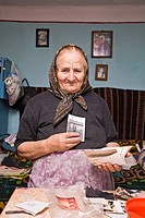 Rumanian woman wearing a headscarf showing her photo album in Bezded, Salaj, Transylvania, Rumania, Europe