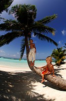 Children on a palm tree trunk in Kurumba Resort, The Maldives, Indian Ocea