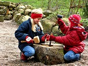 children carving a cave into a trunk to build a breeding cave