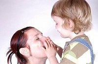 little boy putting skin creme on a red_headed women