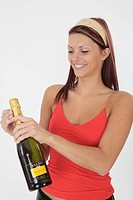 attractive young woman opens a bottle sparkling wine