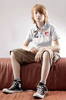 12 year_old boy, sitting on a sofa looking sad