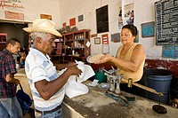 Cuban receiving food for his food vouchers from a saleswoman in a store, Trinidad, Sancti_Spíritus Province, Cuba, Latin America, America
