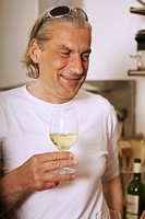 Grey_haired man drinking white wine