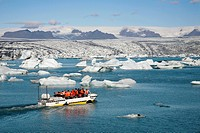 In the Joekulsarlon glacier lagoon of the Vatnajoekull Glacier, people travelling in an boat between the floating icebergs, which are partly coloured ...