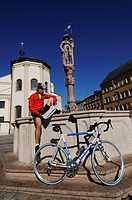 Racing cyclists taking a break at the fountain in the town square of Traunstein, Chiemgau, Bavaria, Germany, Europe