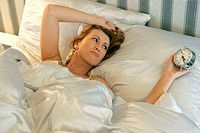 woman awaking by alarm clock in the morning