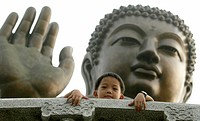 Boy in front of a bronze Buddha at Po Lin Monastery, Lantau Island, fishing village, Hong Kong, China, Asia