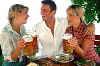 man with 2 women in beer garden