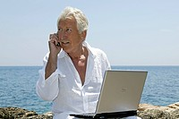 man, senior citizen with notebook at sea side