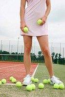 young woman with too many balls at a tennis court