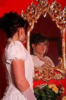 woman wearing a bridal dress regards herself in a mirror