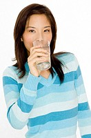 A pretty young asian woman drinking a glass of water