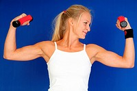 young blond, attractive woman trains with two dumbbells
