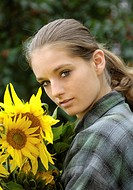 young natural woman with ponytail and karo shirt with a bunch of sunflowers in her arms