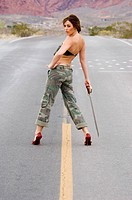 woman with a sword in fatigues on a country road in the desert looking back over her shoulder