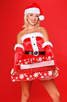 sexy blond Mrs Santa in a red velvet suit, delivering a big arm load of christmas gifts