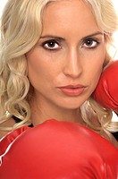 beautiful young woman with red boxing gloves, looks challenging