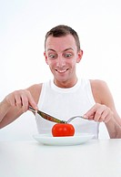 man cutting a tomato at plate