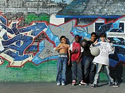 young boys posing with basketball in front of a wall sprayed with graffiti, USA, Bronx, New York