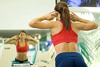 A woman works out in a gym looking at her reflection