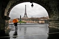 women with a yellow umbrella under the pont de Bir_Hakeim bridge, France, Paris