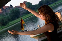 cute brown_haired woman catching the sun, with outstretched arms