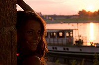 cute brown_haired woman smiling, with a ship on the river in the background