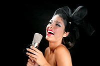 Beautiful woman singing on a vintage microphone on black background