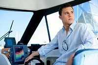 Young handsome man on a yacht boat interior in summer